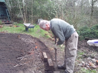 Paul digs out the edge to provide support for the log rolls.