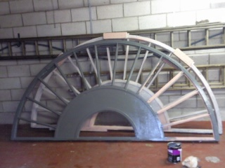 Meanwhile Susan paints primer to the semi-circular wheel in two halves ready to be set in place.